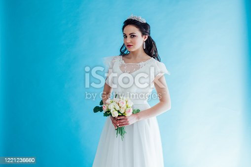 istock Princess Bride in a white dress with a Crown on a blue background 1221236660