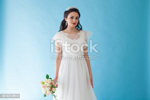 674214372istockphoto Princess Bride in a white dress with a Crown on a blue background 674212812