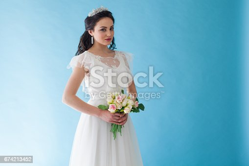 674214372istockphoto Princess Bride in a white dress with a Crown on a blue background 674213452
