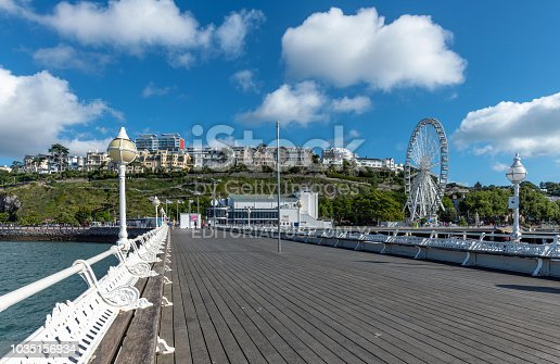 Torquay, UK - September 9, 2018: A view down Princess Pier in Torquay. People walking on the pier in the distance on a sunny day. The town in the background.