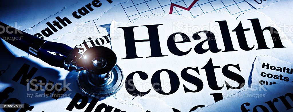 Print headlines on health costs with stethoscope stock photo