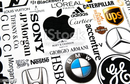 London, England - October 19, 2011: A collection of well-known international brand names printed in a magazine. Names include Louis Vuitton, Johnnie Walker, L'Oreal, Caterpillar, UPS, adidas, Cartier, Apple, Sony, J P Morgan, Tiffany + Co, Gucci, Nestle, Moet et Chandon, Moet + CHandon, Hermes, BMW, Giorgio Armani, Accenture and Harley Davidson. Paper texture and slightly off-set registration visible, with differential focus.