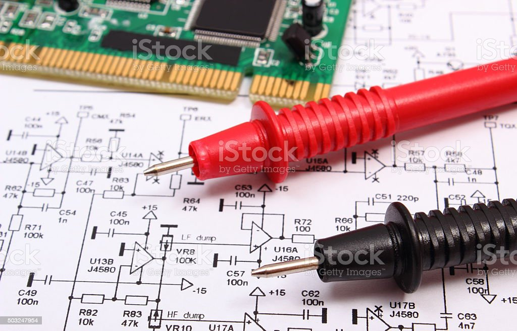 Printed circuit board, cable of multimeter on diagram of electronics stock photo