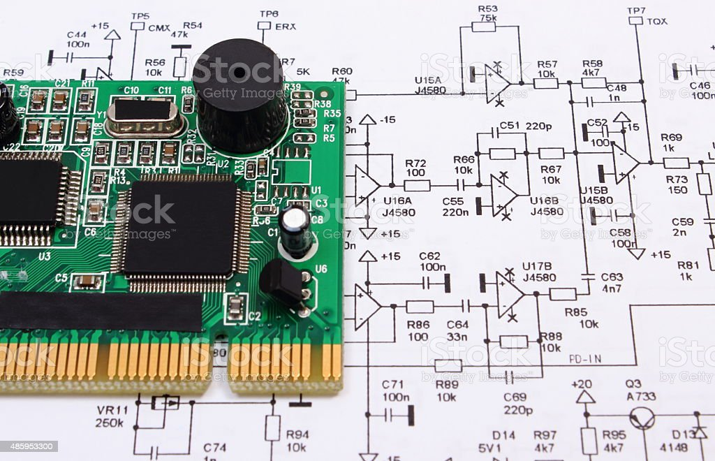 Printed Circuit Board Lying On Diagram Of Electronics Technology Stock Photo