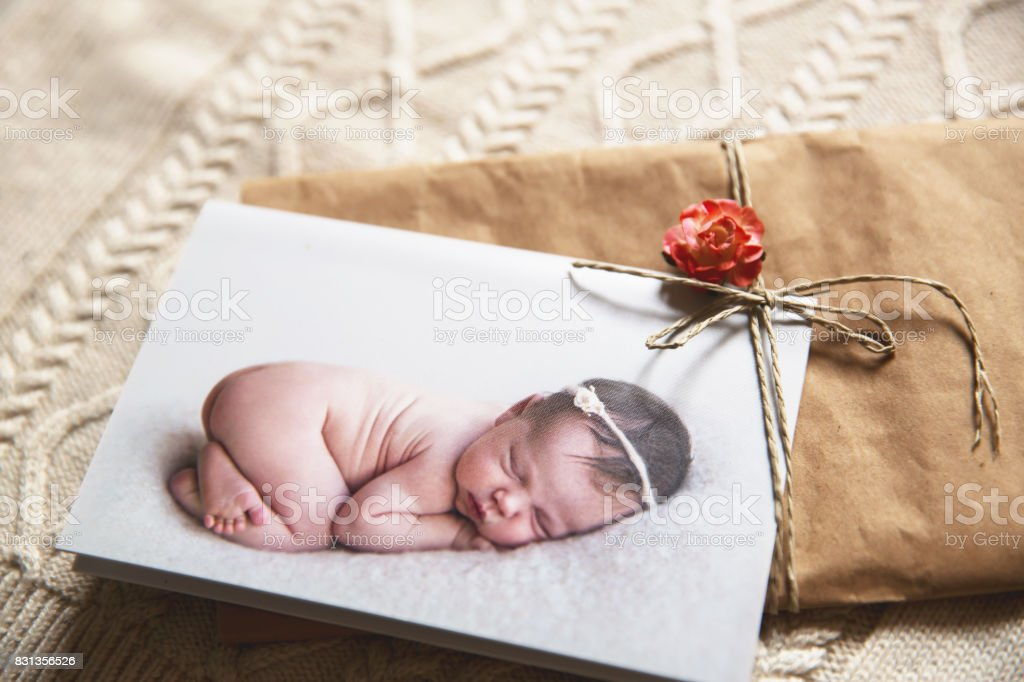 Printed greeting card with cutest sleeping newborn baby on the knitted background. stock photo