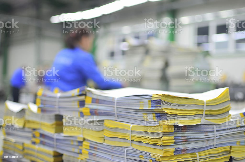 Printed material packets with blur workers at background stock photo