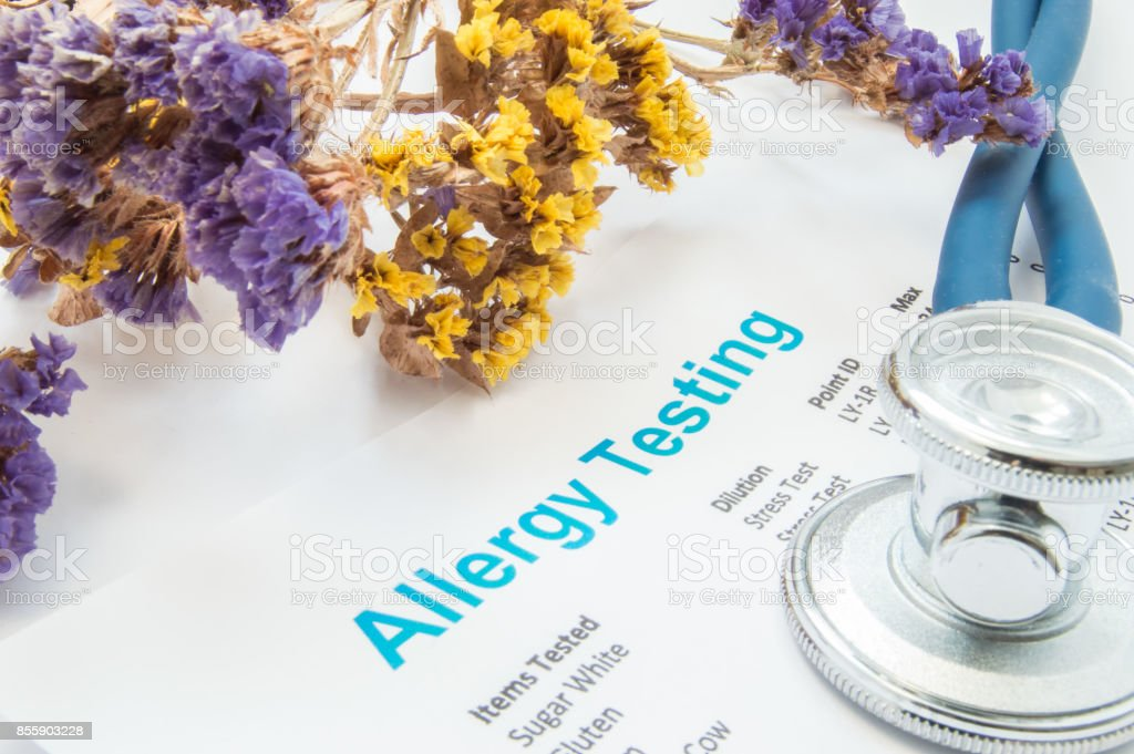 Printed result of allergy test (blood or skin) lies next to flowers with falling pollen and stethoscope. Concept photo for analysis of presence allergies to food, pollen, hair or wools in human stock photo