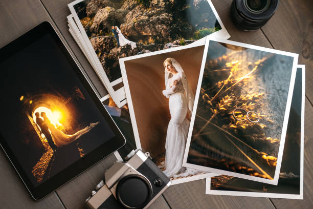 Printed wedding photos with the bride and groom, a vintage black camera and a black tablet with a picture of a wedding couple stock photo