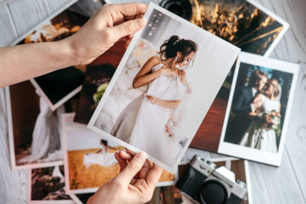 Printed wedding photos with the bride and groom, a vintage black camera and woman hands with photo stock photo
