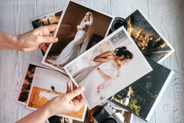 Printed wedding photos with the bride and groom, a vintage black camera and woman hands with two photos stock photo