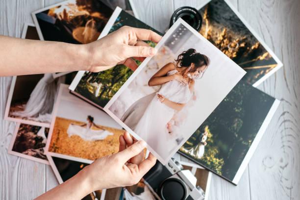 gedruckte hochzeitsfotos mit braut und bräutigam, ein vintage schwarze kamera und frau hände mit foto - fotografische themen stock-fotos und bilder