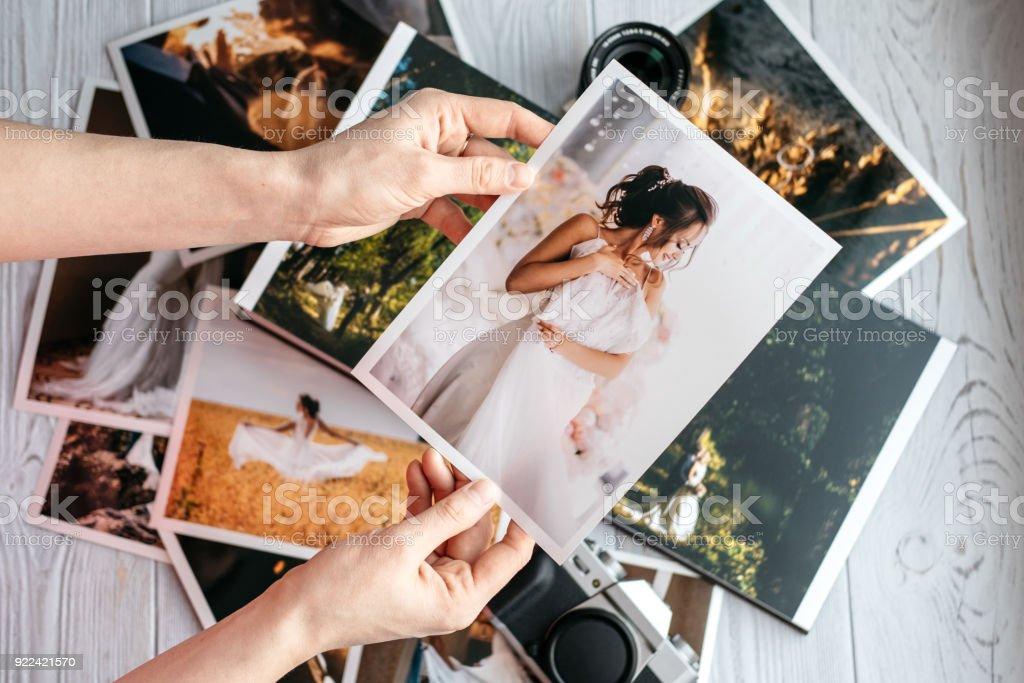 Fotos de boda impresas con la novia y novio, una cámara vintage negro y manos de mujer con foto - foto de stock