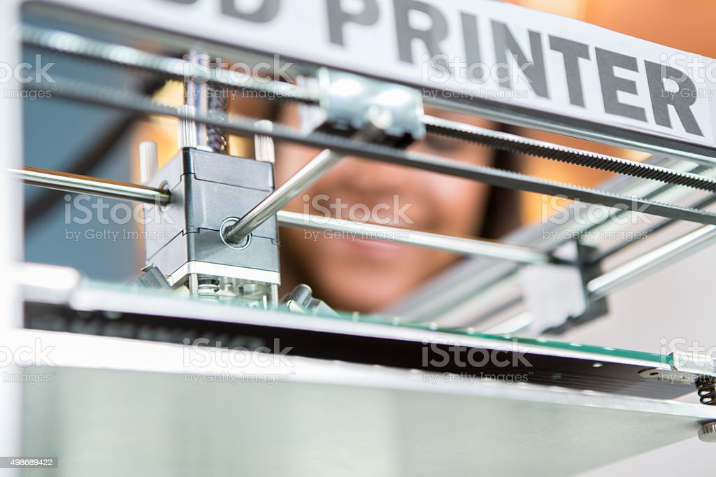 3D printer creating plastic object while student watches stock photo