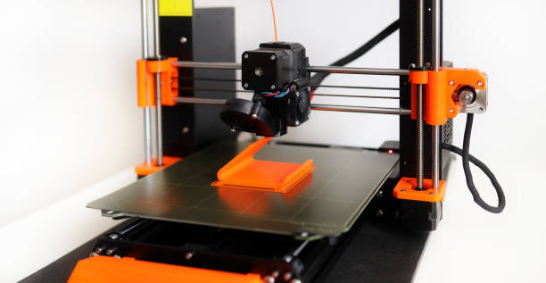 3D Printer in operation with orange filament on a white background stock photo