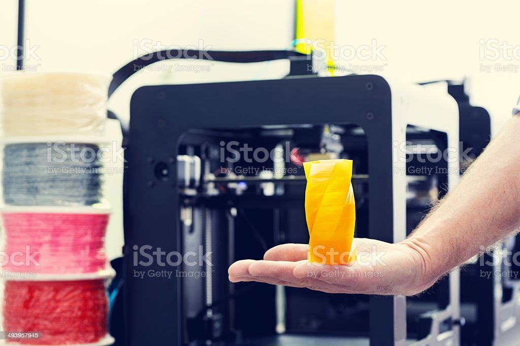 3D printer office Close up of yellow container printed by 3d printer on a human hand with 3d printer machines in the background. 3D Printing Stock Photo