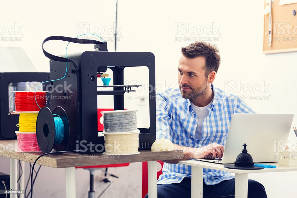 3D printer office Man working in a 3d printer office, watching at 3d printout. 30-39 Years Stock Photo