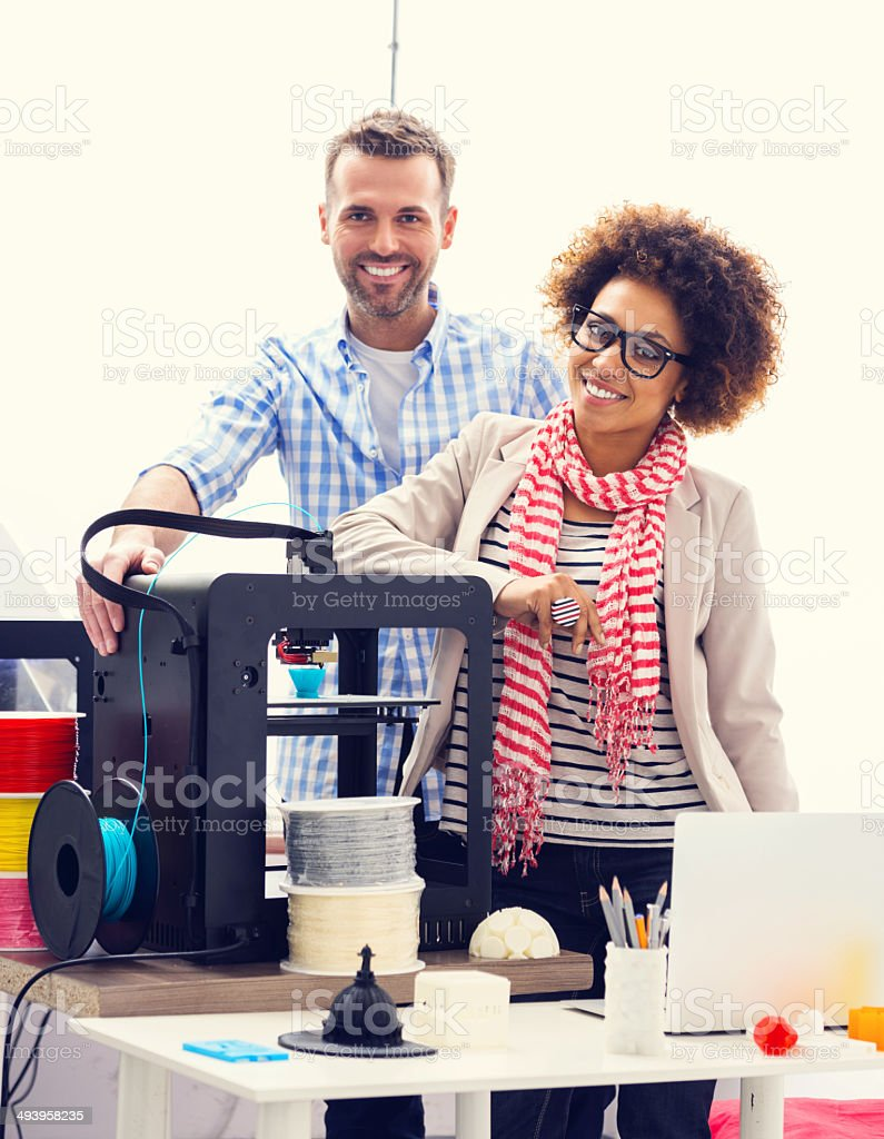 3D printer office Two business colleagues standing next to 3d printer in an office and smiling at the camera. 3D Printing Stock Photo