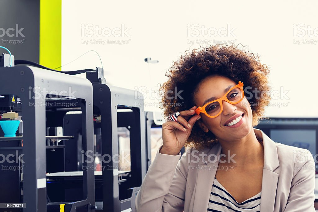 3D printer office Mixed race friendly young woman wearing 3D printed glasses, sitting in a 3D printer office and smiling at the camera. 3D Printing Stock Photo