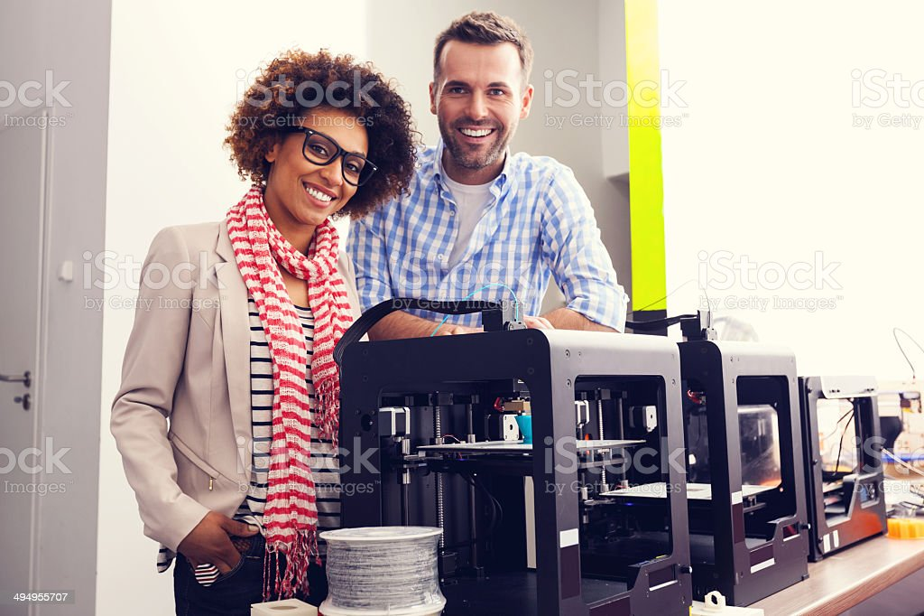 3D printer office Two business colleagues standing next to 3d printer machines and smiling at the camera. 3D Printing Stock Photo