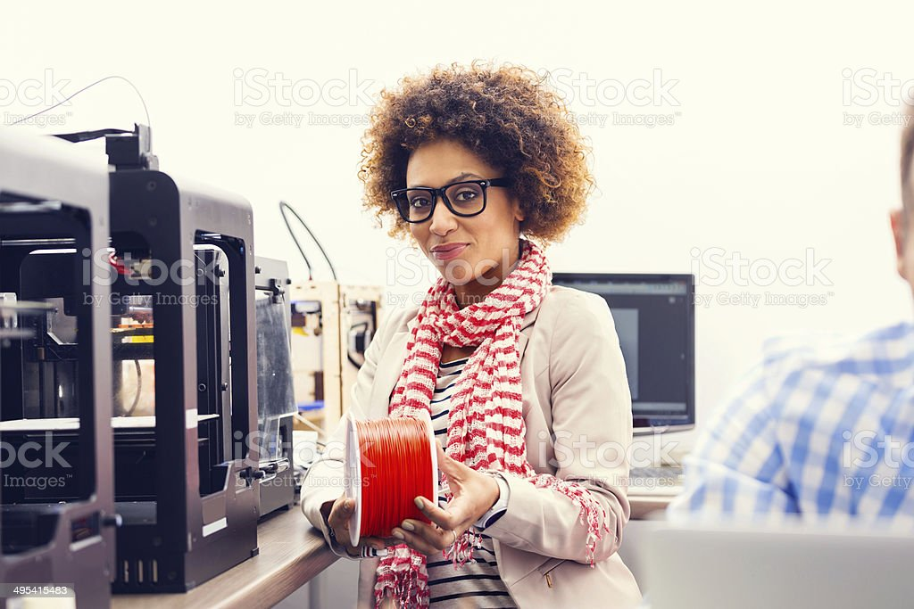 3D printer office Focus on a friendly afro amercian woman sitting at the 3d printer machines, holding a red filament in hands and smiling at the camera. 3D Printing Stock Photo