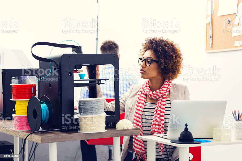 3D printer office Mixed race young woman working in a 3d printer office, watching at 3d printout. 3D Printing Stock Photo