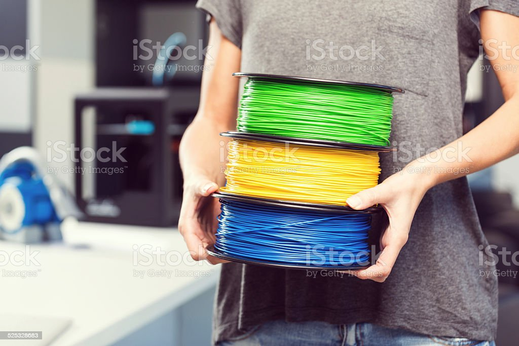3D printer office Close up of female hands holding plastic filaments. 3D printers in the background.  3D Printing Stock Photo