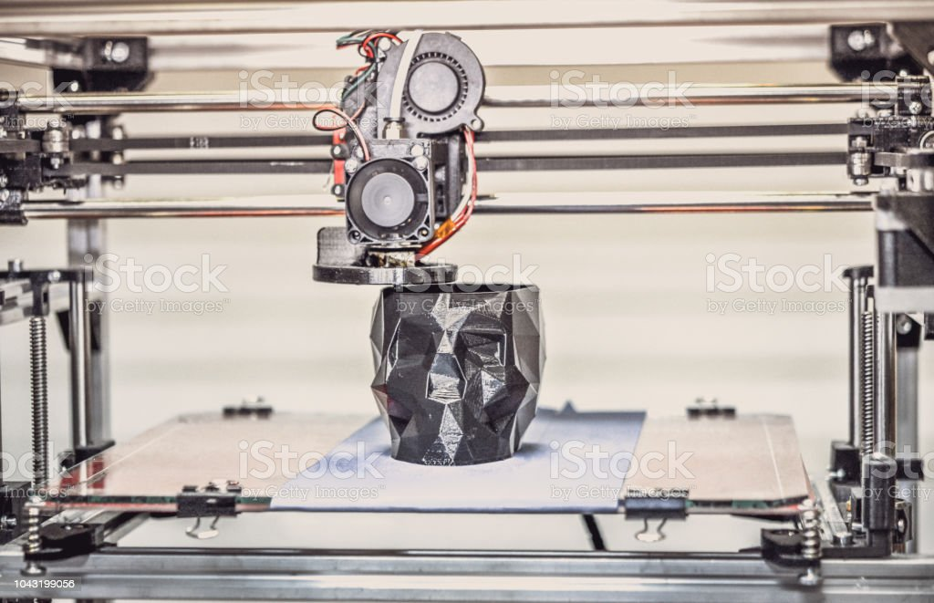 3D printer printing a model in the form of black skull close-up. stock photo