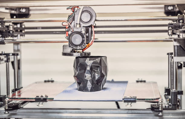3d printer printing a model in the form of black skull close-up. - industrial revolution stock pictures, royalty-free photos & images