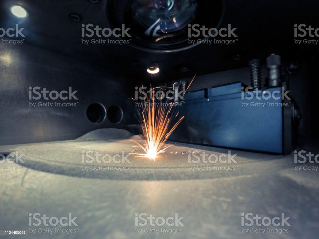 3D printer printing metal. Laser sintering machine for metal. 3D printer printing metal. Laser sintering machine for metal. Metal is sintered under the action of laser into shape. DMLS, SLM, SLS. Modern additive technologies 4.0 industrial revolution. Sparks 3D Printing Stock Photo