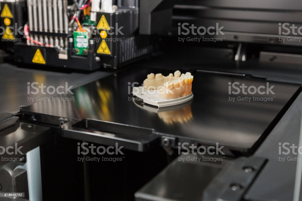 3D Printer With Finished 3D Printed Dental Implant Bridge stock photo