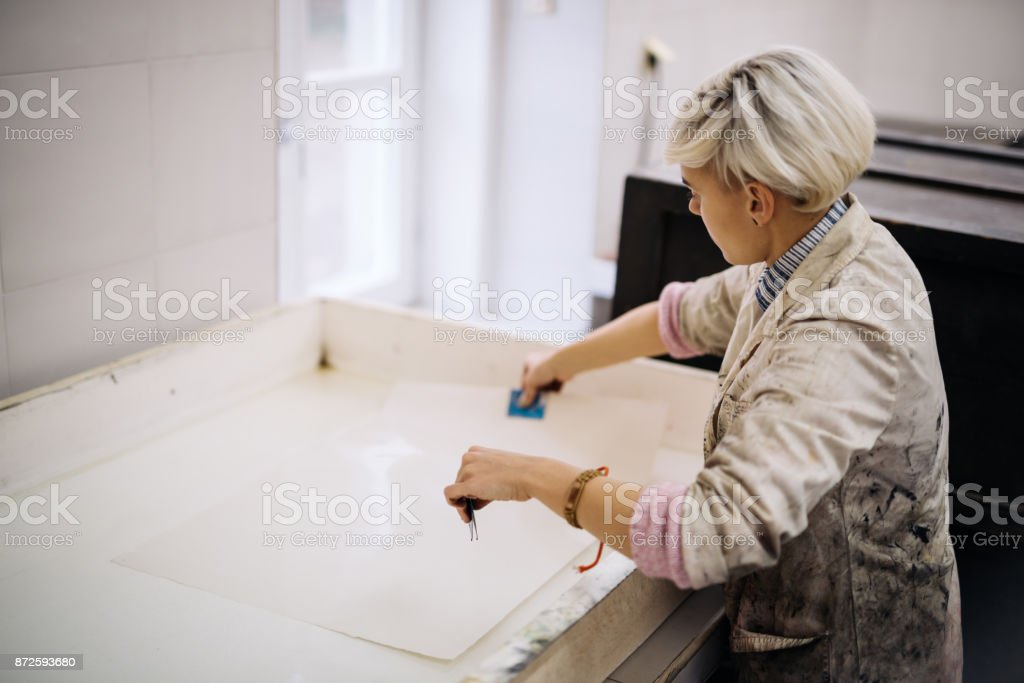 Printing and etching - artist putting paper into chemical solution stock photo