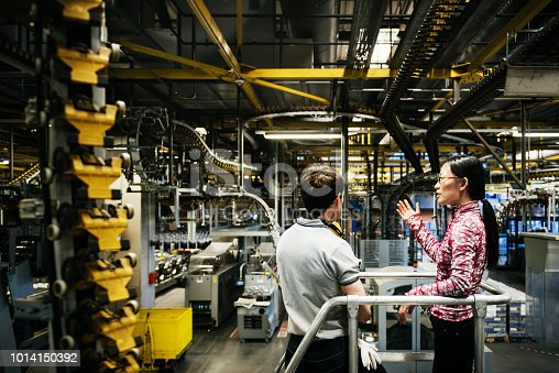 A printing factory engineer talking with his operations manger amongst the machinery.