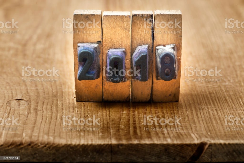 Printing letter '2018' on wooden table stock photo