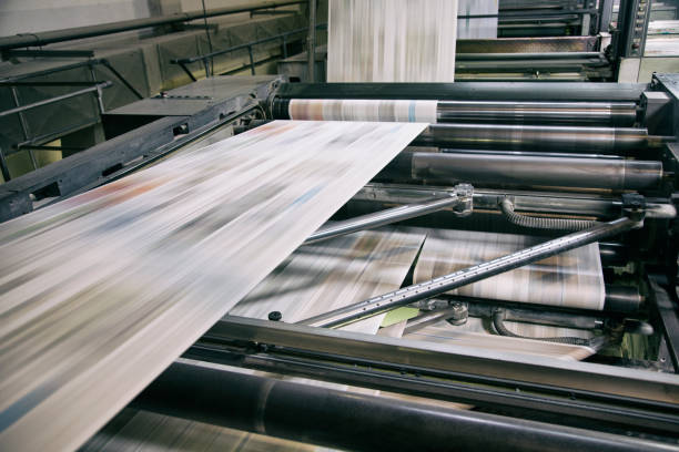 Printing newspapers Newspapers being printed in printing press. newspaper stock pictures, royalty-free photos & images