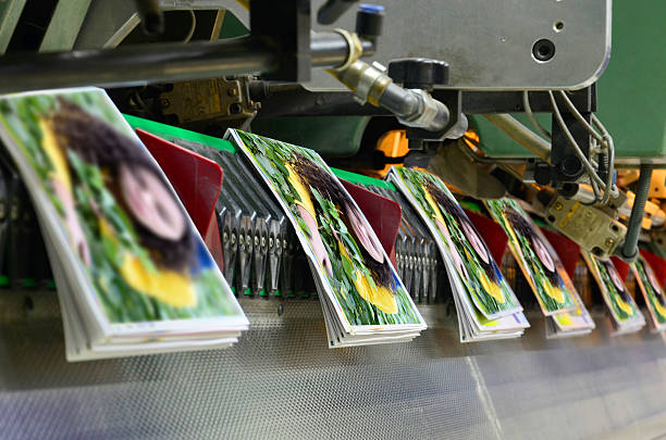 Printing offset conveying plant Brochure and magazine stitching process. Close-up of the  offset conveying process of a full-automatic stitching unit. printing plant stock pictures, royalty-free photos & images