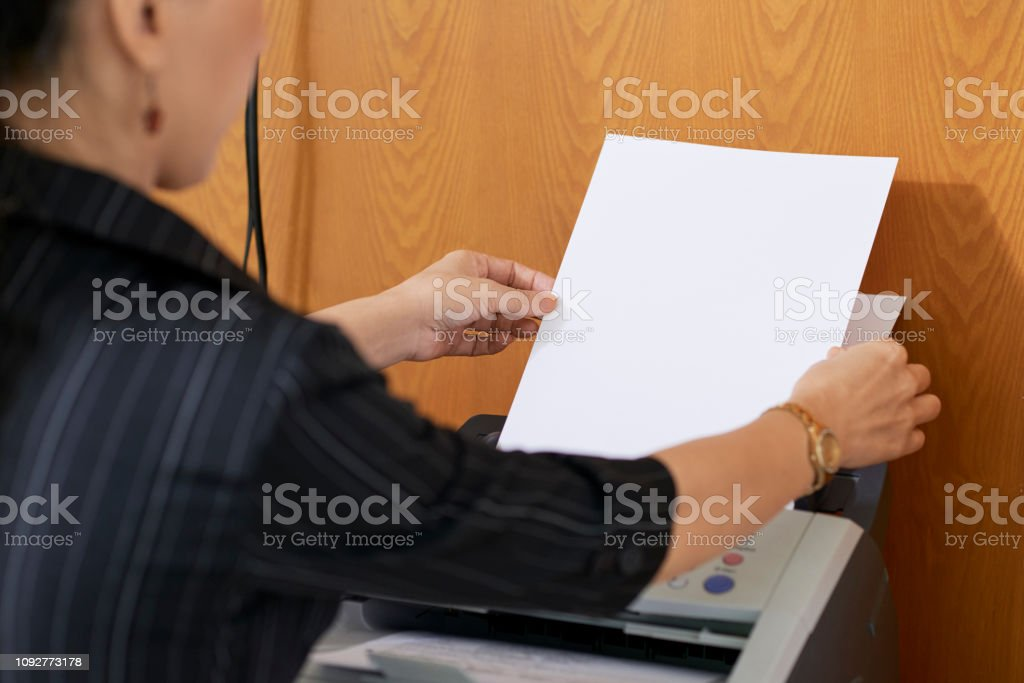 Businesswoman printing out important documents in office