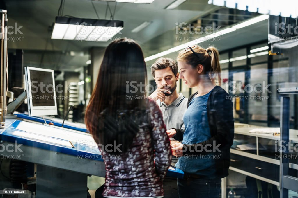 A group of printing plant engineers talking and working together at a...
