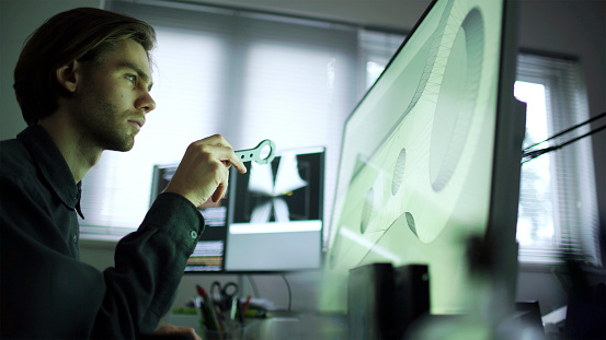 Close up stock photo of a bearded young man working at a wide computer screen. He's working on CAD software designing a component that he's holding in his hand.