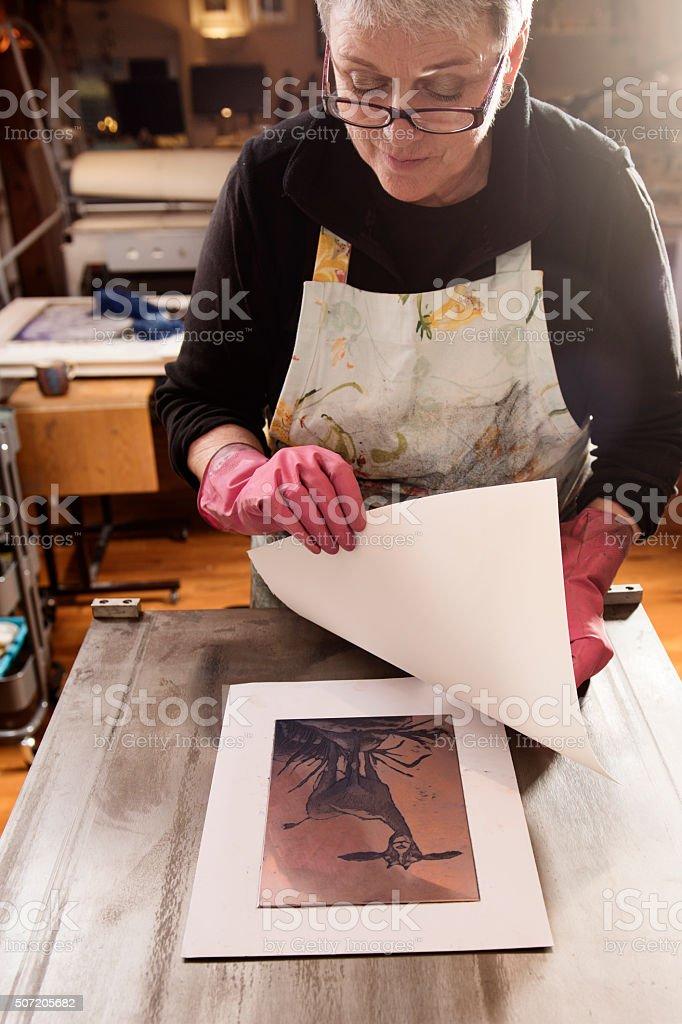 Printmaker Printing an Etching stock photo