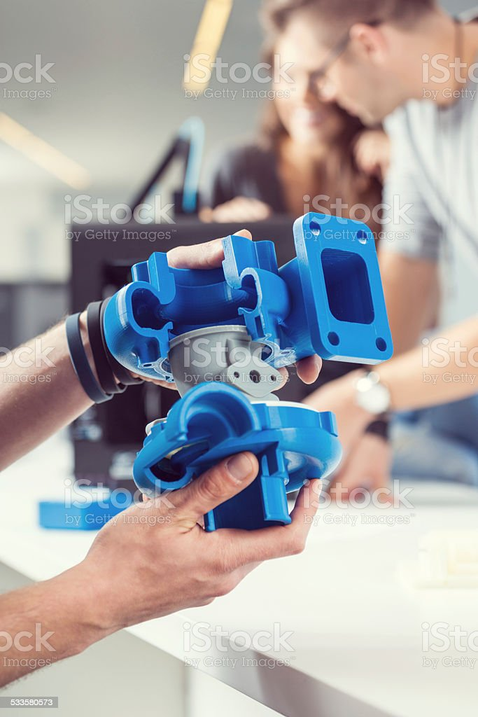 3D printout Close up of male hands holding 3D printout. People working on 3D printer in the background.  2015 Stock Photo