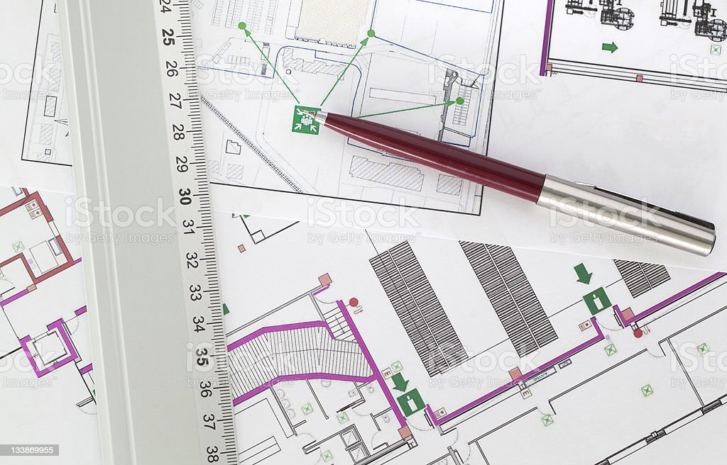 Prints of several evacuation plans with a pen and a ruler stock photo