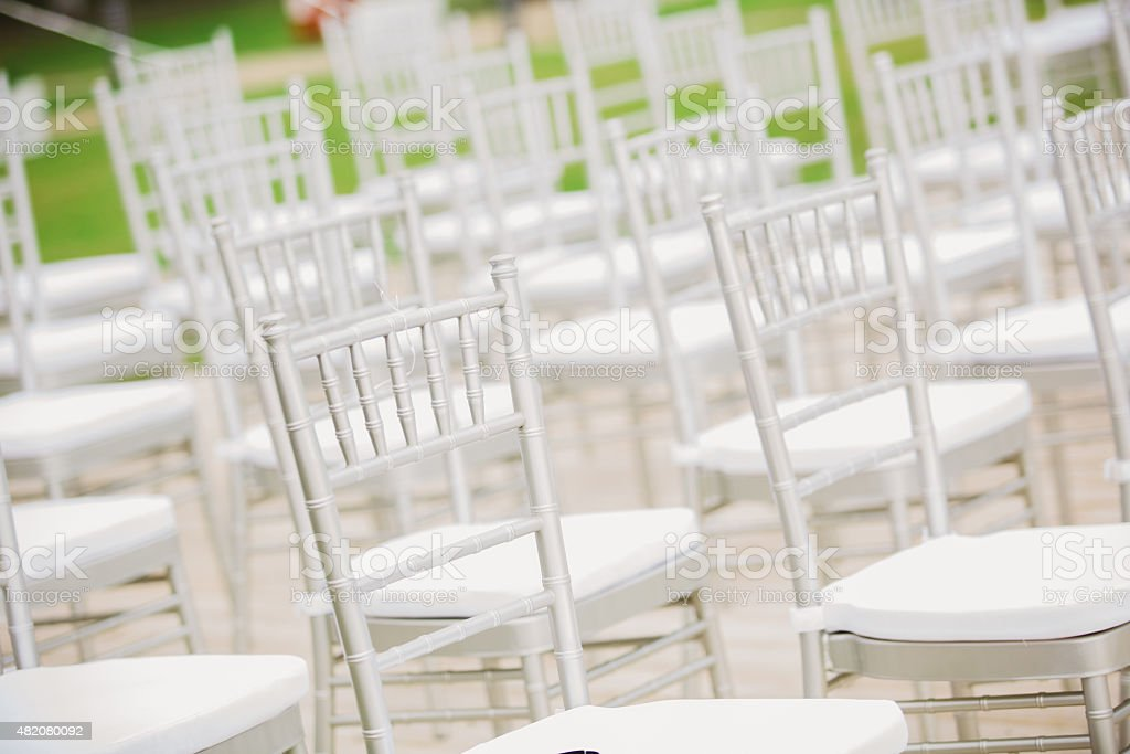 Prior to a wedding ceremony, endless white chairs stock photo