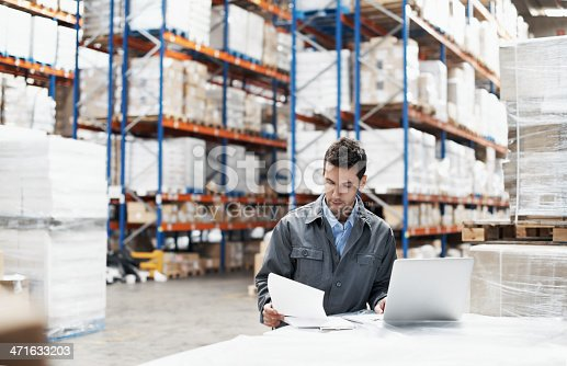 A young man using his laptop and looking over his notes while working in a warehouse