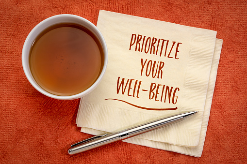 prioritize your well-being inspirational note - handwriting on a napkin with a cup of tea, healthcare, healthy lifestyle and personal development concept
