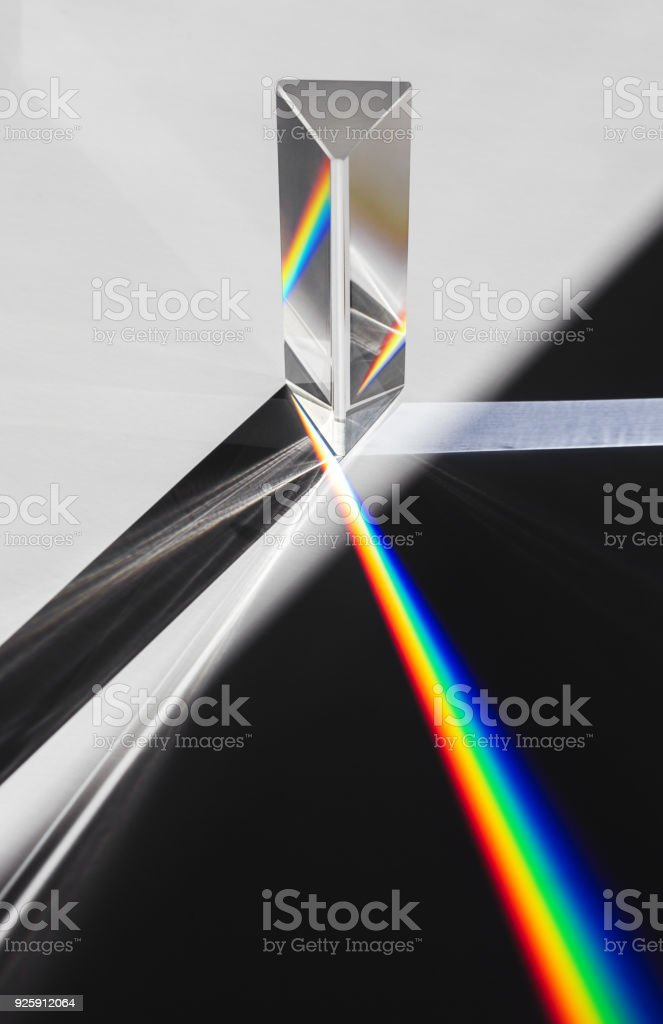 A prism dispersing sunlight splitting into a spectrum on a white background stock photo