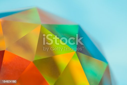 Crystal sphere refracting a riot of colors. A spherical prism. The object is clear glass; natural prismatic coloring.