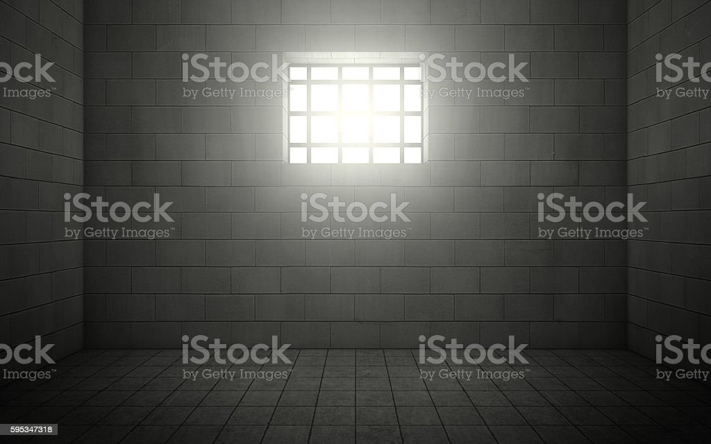 Prison cell with light shining through a barred window stock photo