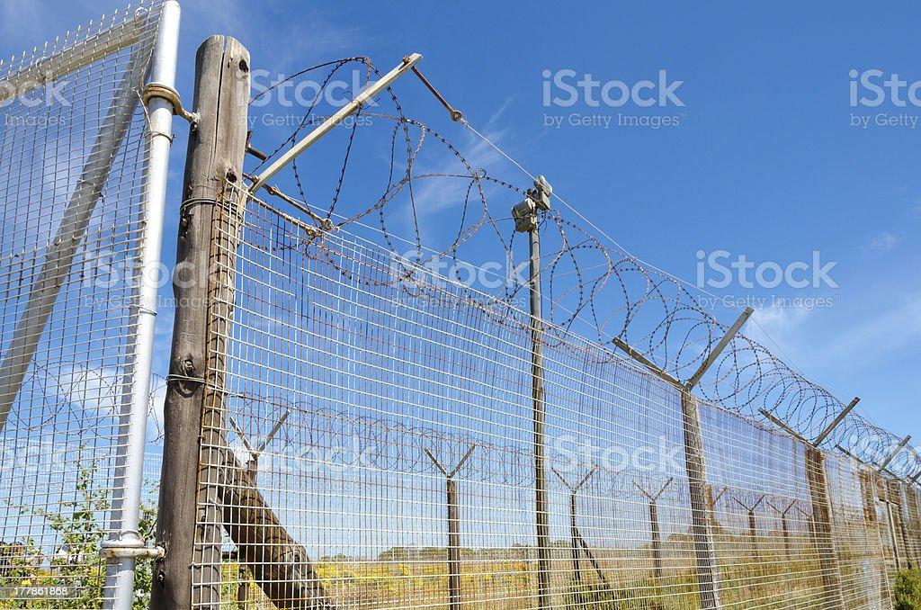 Prison fence razor wire under blue sky on Robben Island stock photo