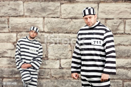 Two convicted felons stand in the prison yard next to the wall that separates them from freedom.