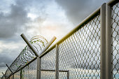 istock Prison security fence. Barbed wire security fence. Razor wire jail fence. Barrier border. Boundary security wall. Prison for arrest criminals or terrorists. Private area. Military zone concept. 1263565472